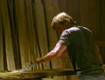 Clay works in his shop, planing boards that will be used to make coffins. (Viggo Mortensen)